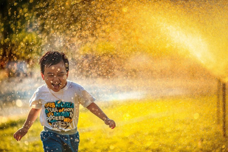 boy filled with joy running through a water sprinkler